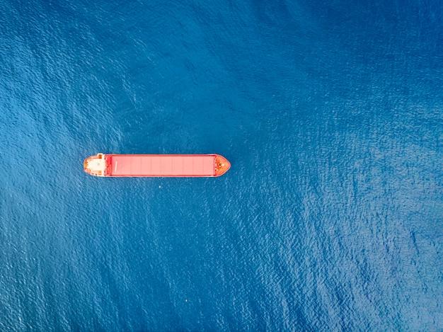 上から撮影した海上での赤い色のコンテナ船。風光明媚な水景と孤独なボートが輸出入ビジネスとロジスティクスに従事。貨物の発送。水運。海とボートの空撮
