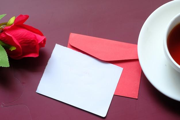 Красный цветной конверт, чай и цветок розы на красном фоне