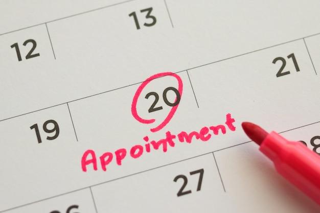 白いカレンダーページの日付の重要な予定のスケジュールを指す赤いカラーマーカーペンのクローズアップ