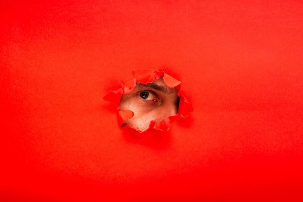 찢어진 구멍이 있는 붉은 색 종이와 그것을 보는 눈, 소문과 엿보는 개념. 재미있는 프로젝트를 찾는 여성의 눈을 그린 재미있는 그림.