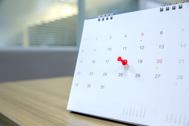 Red color pin on the calendar event planner is busy.