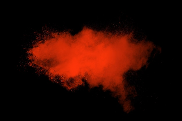 Red color powder explosion on black background