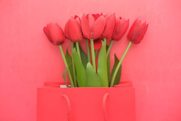 Цветок тюльпана красного цвета в сумке для покупок на красном с копией пространства