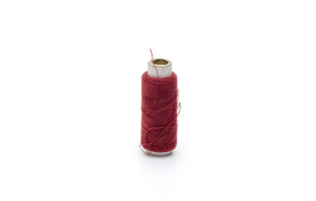 Red color yarn threads spool on isolated white background