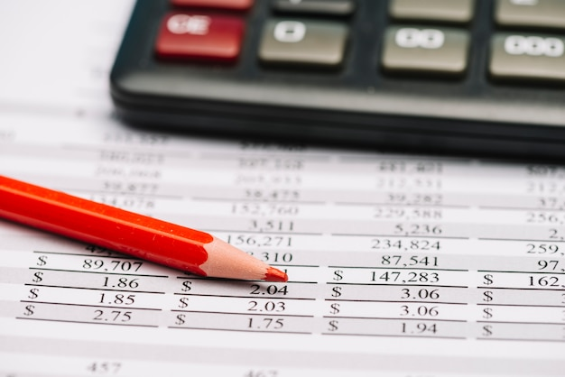 Red colored pencil and calculator over the financial report