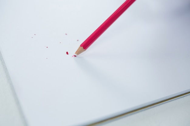 Red colored pencil with broken tip with notebook