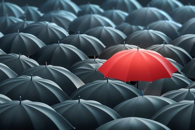 Red colored umbrella between the black umbrellas