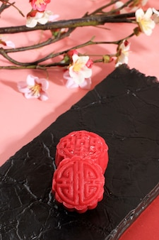 Красный красочный торт snowskin moon. новая вариация лунного пирога, заварного крема с начинкой из теста моти, красной фасоли или пасты из фасоли мунг. отформован в форме лунного пирога.