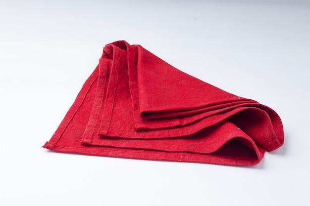 Салфетка красного цвета расположена на белом текстурированном фоне, изолированном, селективном фокусе.