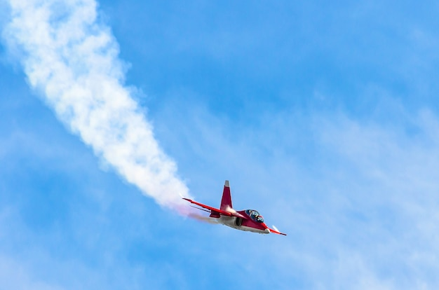Red combat fighter with white smoke behind in the blue sky.
