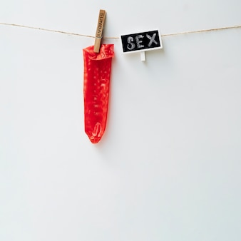 Red condom on clothesline with clothes-pin