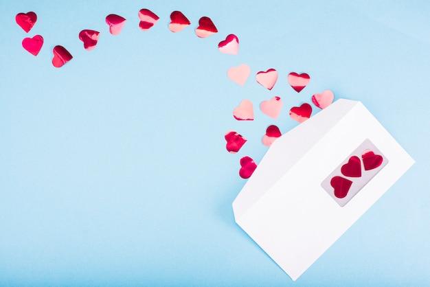 Красные сердца конфетти вылетают из белого конверта на голубой столик. день святого валентина. концепция любви подарок, сообщение для любовника.