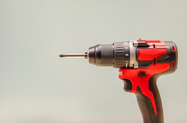 Красная аккумуляторная дрель на черном фоне. инструмент для затяжки винтов, копировальное пространство
