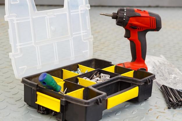 보관 상자에 나사가있는 빨간색 무선 드라이버