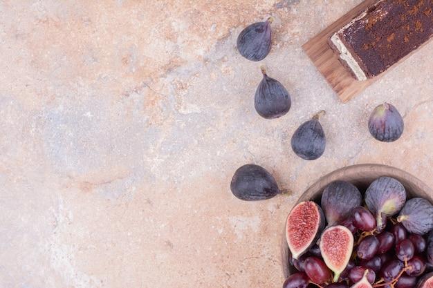 Красные ягоды кизила и фиолетовый инжир в деревянном блюде.