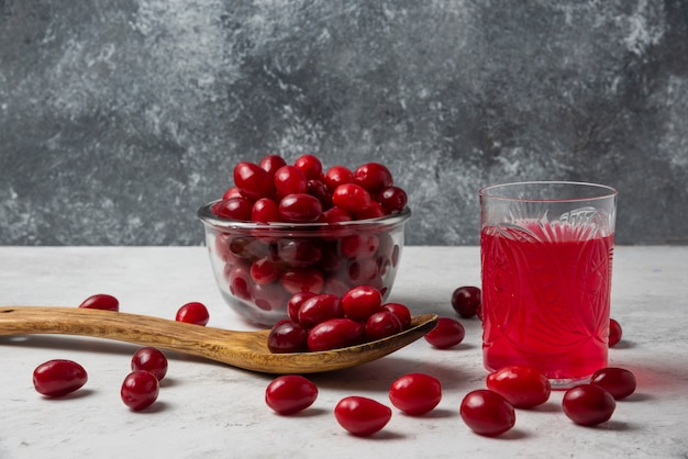 Red cornel berries in a glass cup with juice aside.