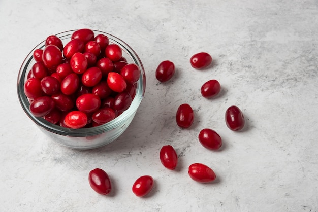 Красные ягоды кизила в стеклянной чашке.