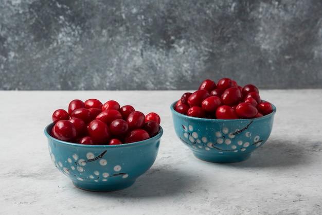 Красные ягоды кизила в синих чашках.