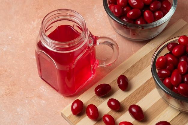 Cornioli rossi e un barattolo di bevanda.