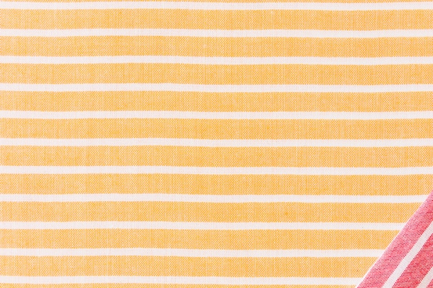 Red corner fabric on yellow and white stripes textile backdrop