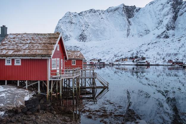 어촌 마을과 눈 산에서 해안선에 빨간 오두막