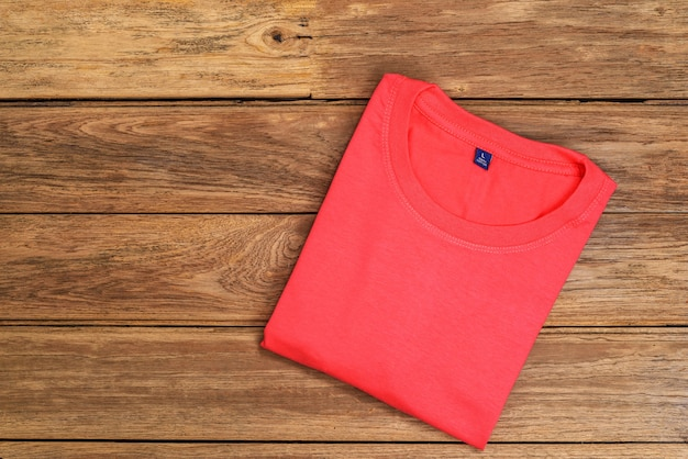 木製の背景に置かれた赤い綿のtシャツ。