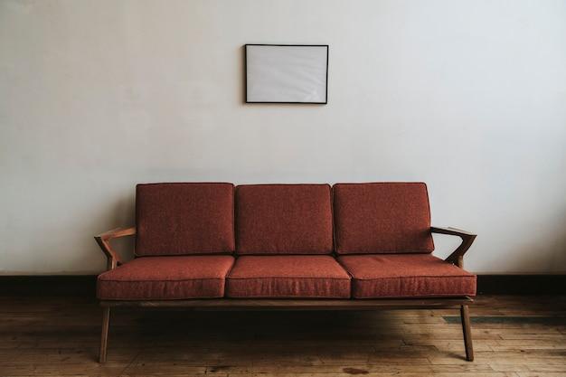 白い壁のそばの赤いソファ