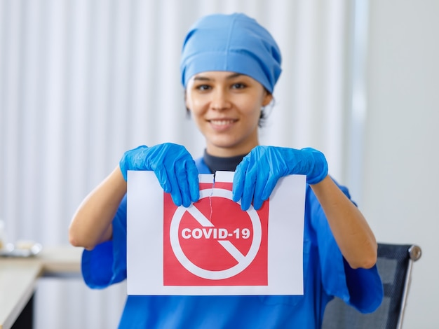 Red covid-19 paper sign was torn apart by happy beautiful doctor in blue hospital uniform in blurred background when coronavirus pandemic has ended and normal life and business open safety.