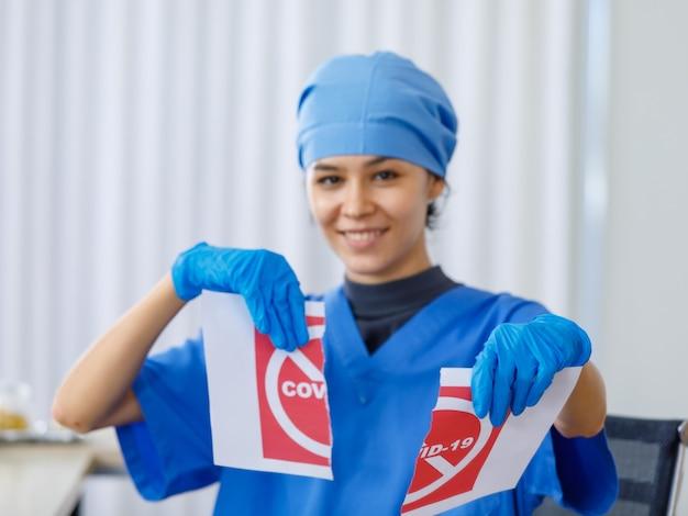 赤いcovid-19紙の看板は、コロナウイルスのパンデミックが終了し、通常の生活とビジネスの安全を開くときに、ぼやけた背景の青い病院の制服を着た幸せな美しい医者によって引き裂かれました。