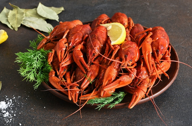 Red crayfish with dill, bay leaf and lemon in a plate.