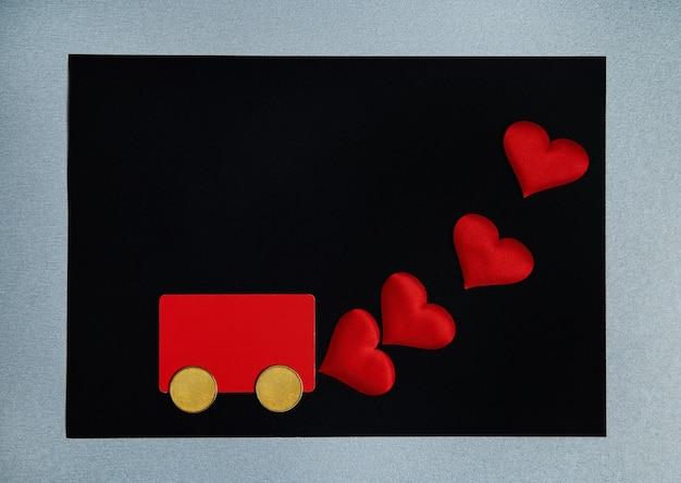 Красная кредитная карта и две монеты в виде колеса символизируют машину, испаряющую сердца. концепция дня святого валентина.
