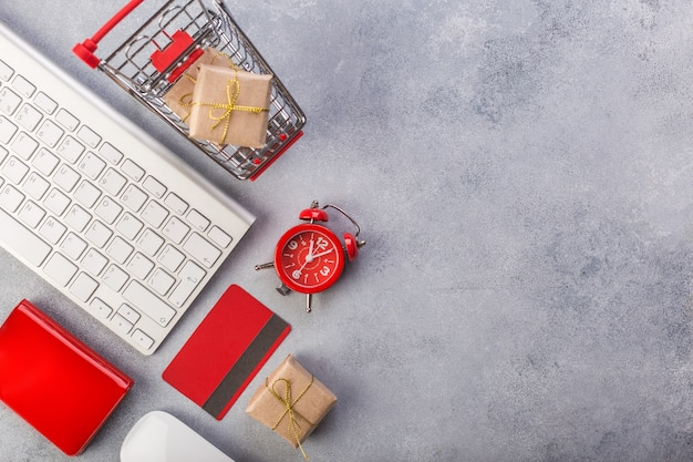 Red credit card, keyboard and christmas presents on grey table flat lay, copy space.