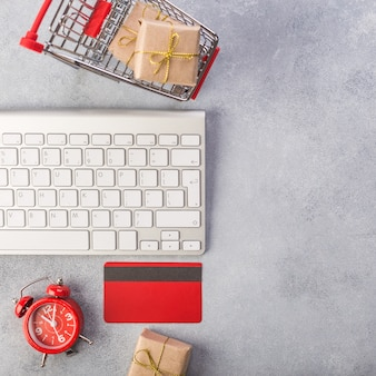 Red credit card, keyboard and christmas presents on grey table flat lay, copy space