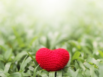 Red crocheted heart shape in green grass