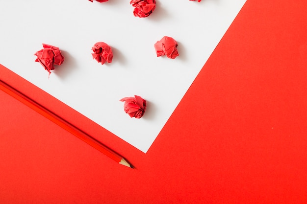 연필로 흰색과 빨간색 이중 종이 배경에 빨간색 구겨진 종이