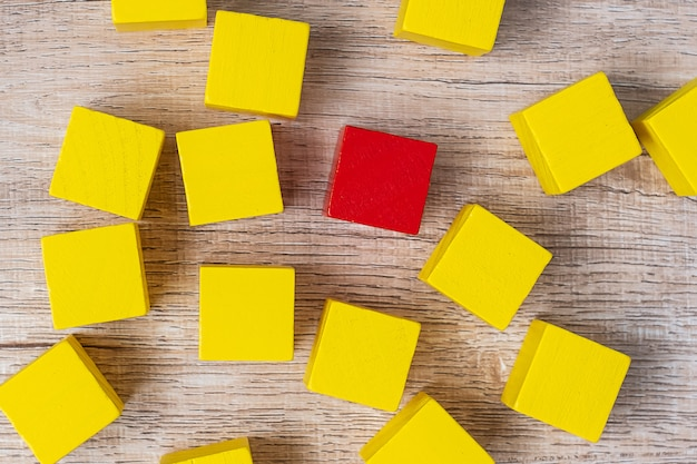 Red cube block different from crowd of yellow blocks. unique leader, strategy, independence, think different, business and success