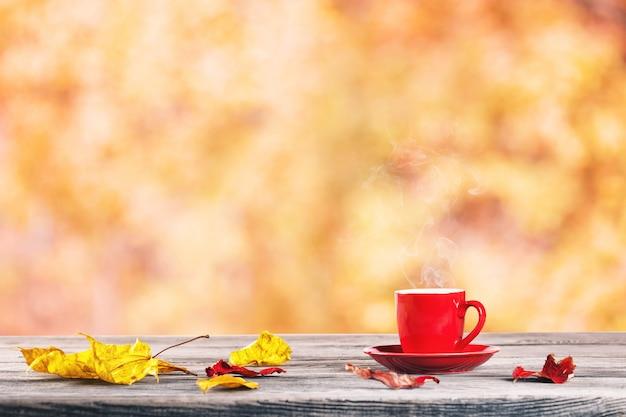 Красная чашка и осенние листья на столе