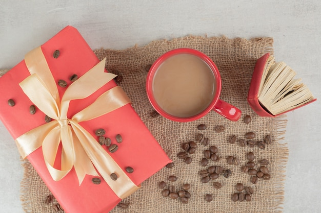 Red cup, book and coffee beans with gift box