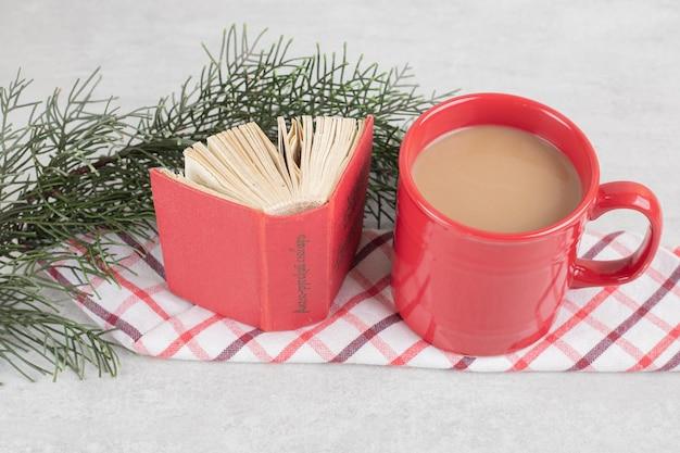 Tazza rossa e libro sulla tovaglia con ramo di pino