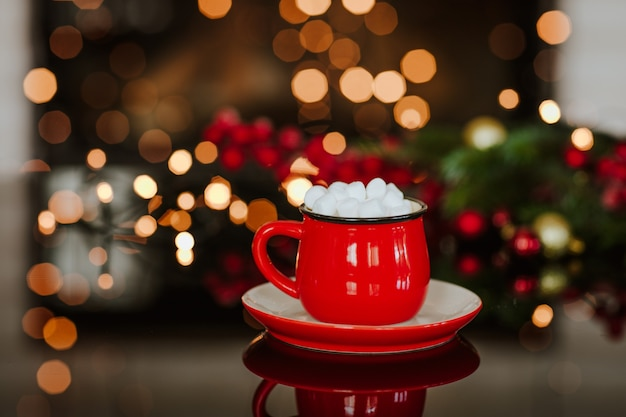 Red cup of cacao with marshmallows standing on black mirror table against christmas lights. copy space.