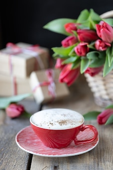 Red cup of coffee close-up, a bouquet of red tulip and gift boxes on wooden background