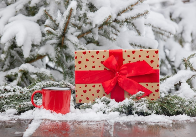 Red cup of coffee and gift box on wooden table in snow