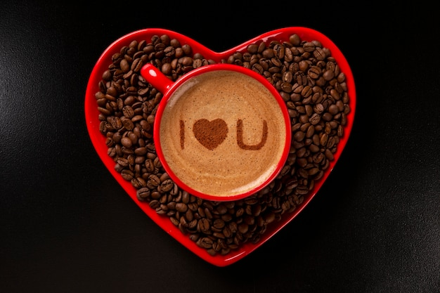 Red cup and coffee saucer in heart shape with decorated coffee on black space. top view. written i love you shape in coffee in english.