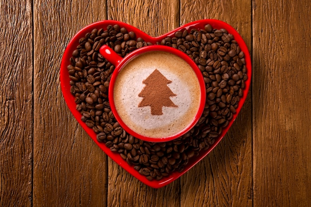 Red cup and coffee saucer in heart shape with decorated coffee on old wood surface