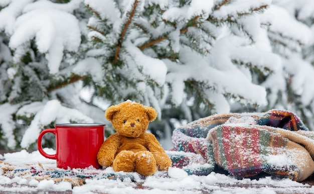Red cup of coffee and scarf with teddy bear on wooden table in blizzard