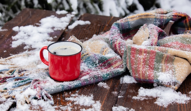 Red cup of coffee and scarf on wooden table in blizzard