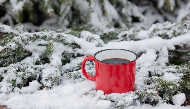 Red cup of coffee and snow around on wooden table in blizzard