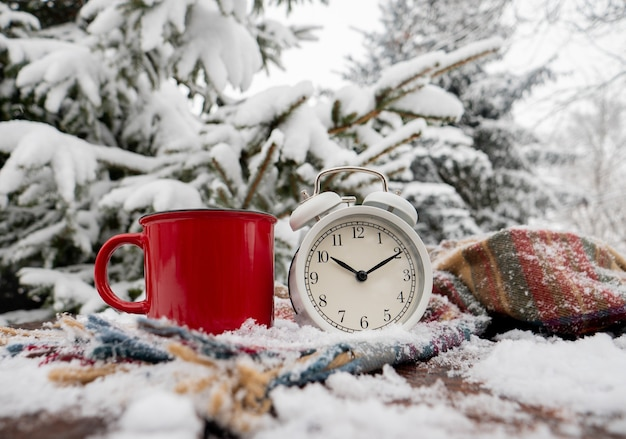 Red cup of coffee and vintage alarm clock with scarf on wooden table in blizzard