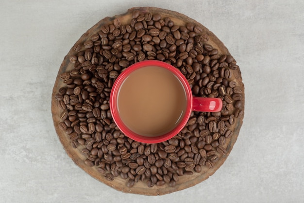 Tazza di caffè rossa con chicchi di caffè sul pezzo di legno