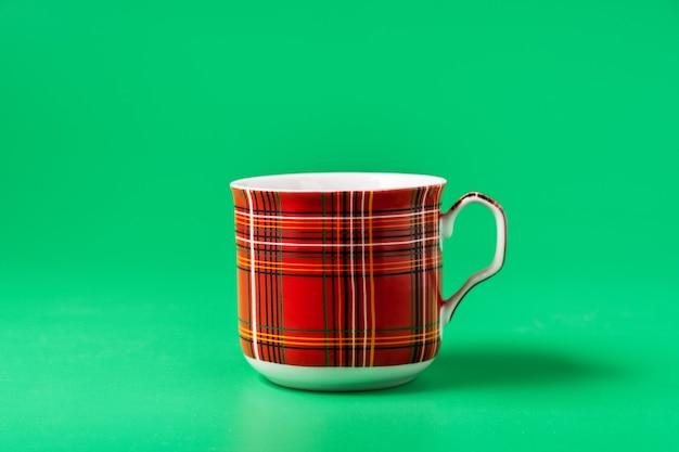 Красная чашка для чая или кофе на зеленом фоне, вид спереди.